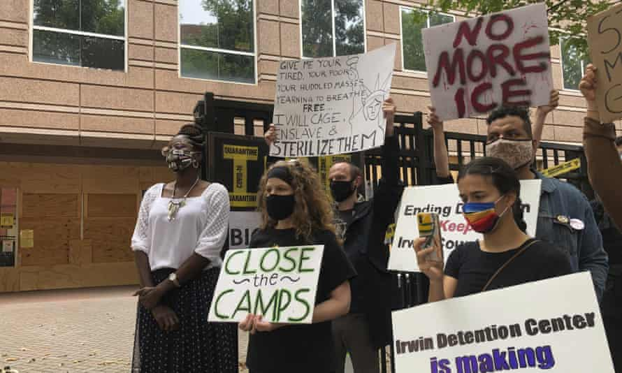 People hold signs as Dawn Wooten, left, a nurse at Irwin county detention center in Ocilla, Georgia, speaks at a news conference in Atlanta.