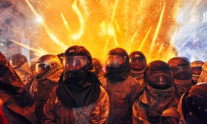 Tainan, Taiwan. Participants at the dangerous Yanshui Beehive Fireworks Festival in Yanshui District wear motorcycle helmets, fire-retardant clothing and thick gloves