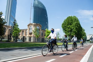 Four cyclists wearing protective masks ride along a new cycle path in Milan.
