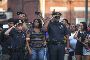 Police officers Jamie Pacucci and Reggie Eiland comfort Angel Warren, the fiancee of slain police officer Calvin Hall, who died after being shot while off duty in Homewood, during a ceremony in front of the police station, on the north side of Pittsburgh.