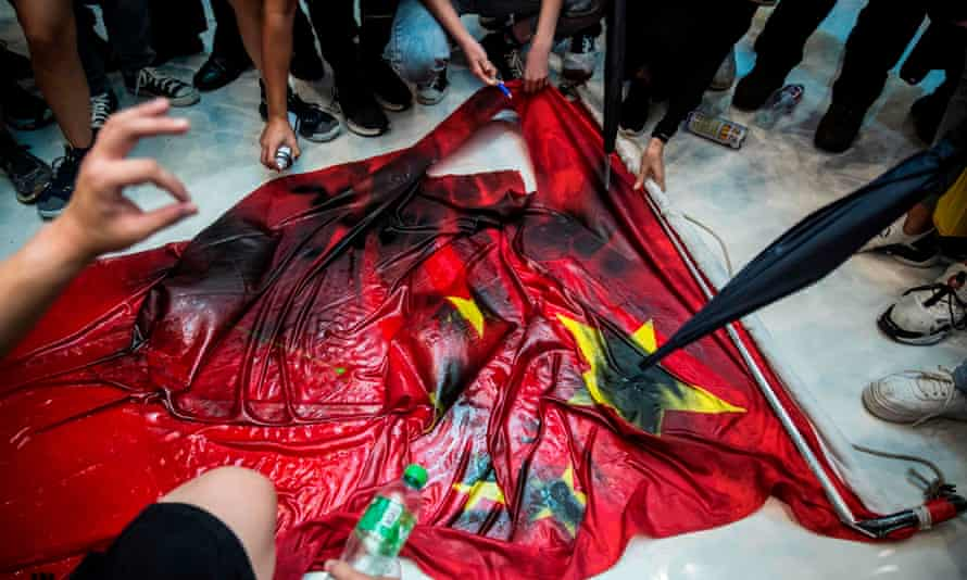 Protesters deface a Chinese flag at the New Town Plaza shopping mall in Hong Kong's Sha Tin district