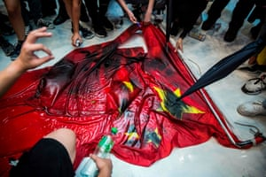 Pro-democracy protesters deface the Chinese flag during a protest in Hong Kong's Sha Tin district on Sunday.