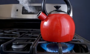 A red teapot is on the boil and steam is pouring out of the spout