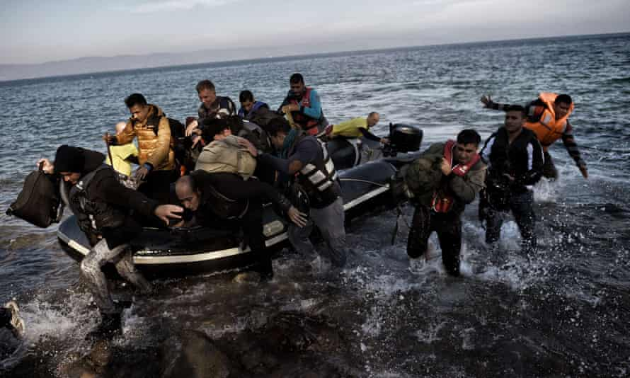 Refugees and migrants jump off a dinghy at the Greek island of Lesbos, after crossing the Aegean Sea from Turkey.