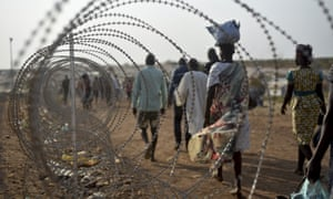 Displaced people walk next to a razor wire fence at the UN compound in Juba.