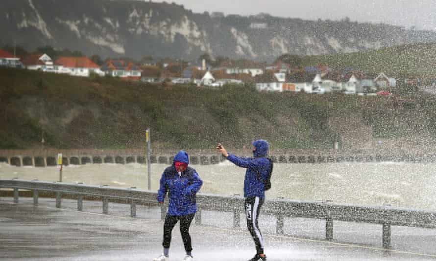 People take pictures of the waves hitting the harbour wall in Folkestone, Kent