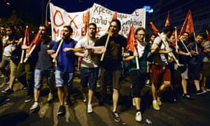 Protesters march, holding banners and flags in front of the Greek parliament