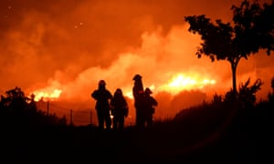 Los Angeles county firefighters keep watch on the Bobcat Fire as it burns through the night in Juniper Hills, California on 19 September.