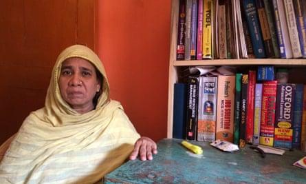 Halima Begum sits beside the books and desk of her son Muhammad Hafizur Rahman.