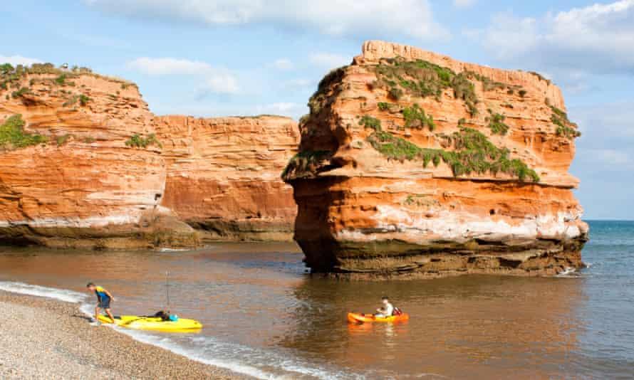 People landing kayaks by the sea stacks at Ladram Bay.