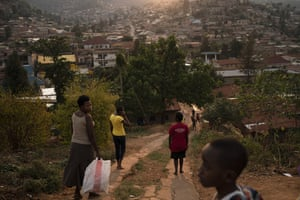 Residents walk down a hill as the sun sets