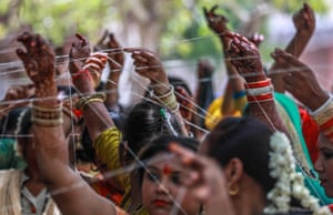 Ahmedabad, India. Women perform rituals around a banyan tree on the fasting day of Vat Savitri, when married Hindu women offer prayers for the long life of their husbands