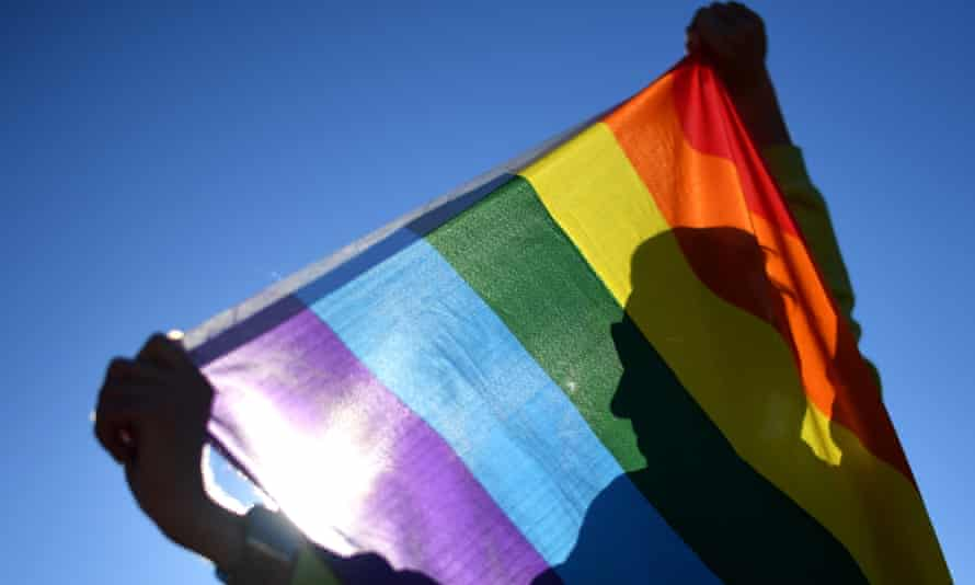 a man in silhouette poses with a rainbow flag