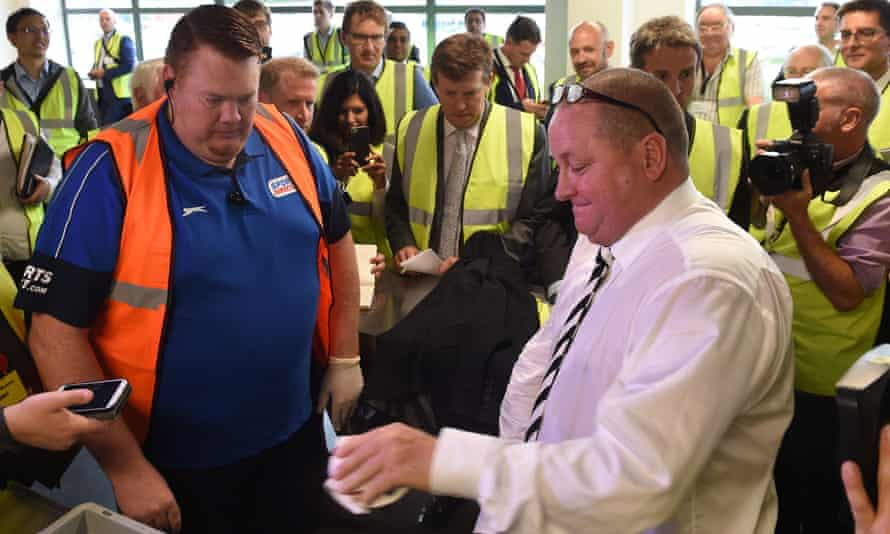 Mike Ashley empties his pockets of bank notes during a mock search at the Sports Direct warehouse in Shirebrook in 2016.