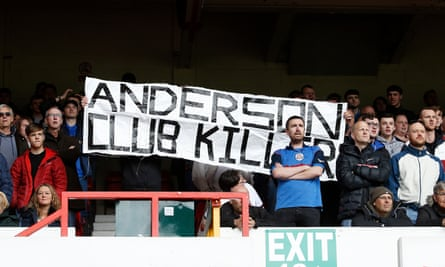 Bolton fans hold aloft a banner expressing their frustration at the club's chairman Ken Anderson.