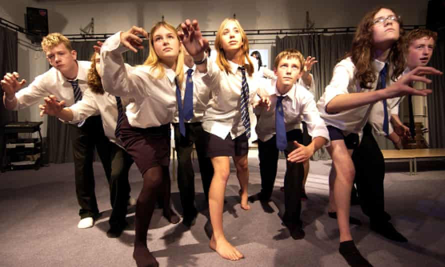 Teenagers in school uniforms in a drama lesson