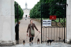 A woman with three dogs leaves the polling station at Burton Court pavilion