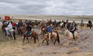 Jake Frazier (centre wearing blue), chairman of the Cheyenne River reservation circles up after a day of riding, along with other Fort Laramie treaty riders, in Harrison, Nebraska. Frazier rode almost the entire way from the Cheyenne River Reservation to Fort Laramie