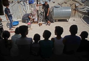 Syrian boys watch two men as they skin a sacrificed sheep at a camp for Internally Displaced Persons in Syria's Idlib province on 12 August 2019.