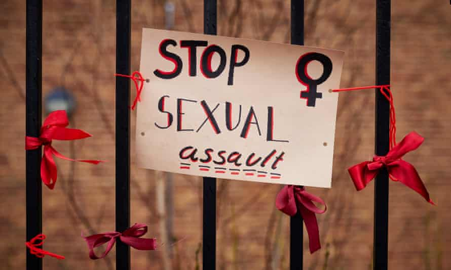 Protest poster reading Stop Sexual Assault and ribbons on the railings of a girls' school.