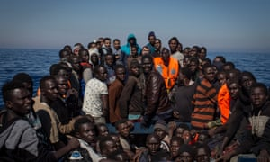 Refugees and migrants wait to be rescued from a small wooden boat by crew members from the Migrant Offshore Aid Station (MOAS) Phoenix vessel on 18 May 2017 off Lampedusa, Italy.