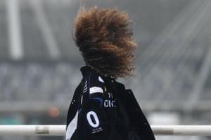 A woman's hair is blown by a gust of wind as she walks across Waterloo Bridge in London