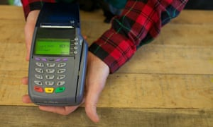 a worker holds out a credit card payment machine