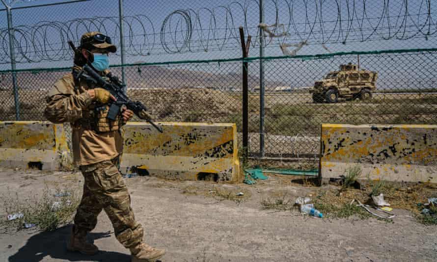 Los combatientes talibanes aseguran el perímetro exterior, a la vista de las fuerzas estadounidenses que controlan el aeropuerto internacional Hamid Karzai en Kabul, Afganistán.