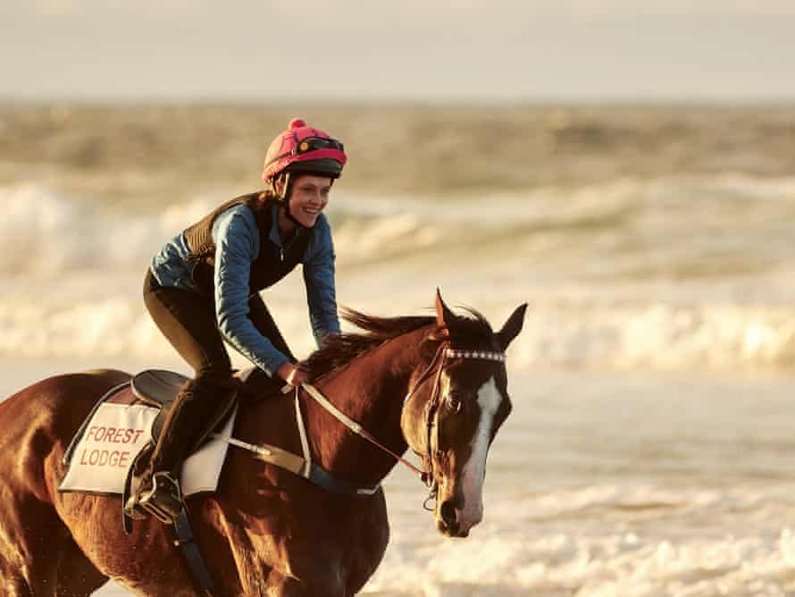 A woman riding a horse in the surf