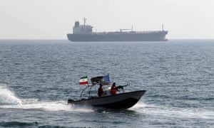 File photo of Iranian Revolutionary Guards driving a speedboat in front of an oil tanker.