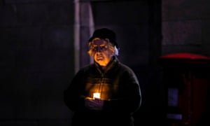 A woman holds a candle outside the Lichfield Cathedral, as part of a day of reflection.