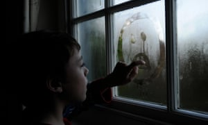 10 year old boy drawing faces in the condensation on a window.