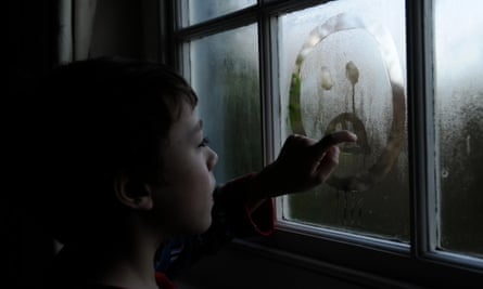 A child draws a sad face on a window