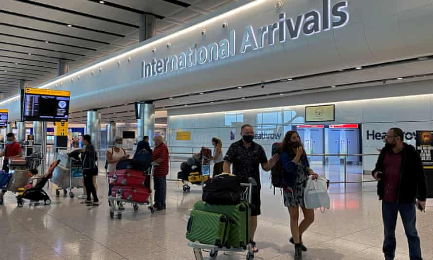 Passengers arrive from international flights at Heathrow airport.