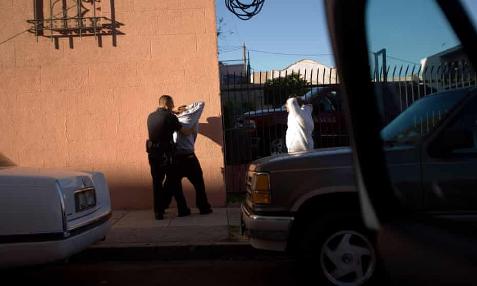 Los Angeles police department gang unit officers stop and frisk someone in the Rampart district of Los Angeles, California, 5 August 2006.