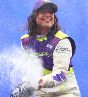 Jamie Chadwick in her racing gear and cap, smiling broadly as she opens a bottle of Champagne, spraying its contents, after winning the inaugural W Series.