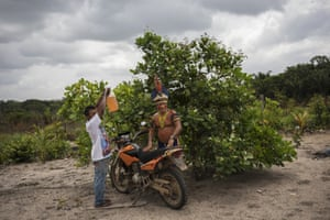 """Cajueiro chieftain Sergio Muxi Tembe, stand by as the tank of his motorcycle is filled with gas, in Para state, Brazil. """"We know Bolsonaro doesn't like Indians. He's anti-Indian,"""" said the chief, wearing a headdress of macaw and other feathers and a traditional bone bracelet on his wrist next to a Casio digital watch. """"We have a different culture and that culture must be respected."""""""