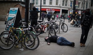 A man who has taken spice lies flat out on the pavement on Piccadilly Gardens, Manchester