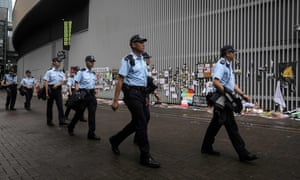 Police walk around the perimeter of the government headquarters one day after protesters broke into the building