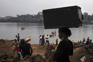 An unidentified woman carries her belongings on her head after crossing the Mbomou river back into Bangassou from Ndu in the Democratic Republic of the Congo, where she had taken refuge.