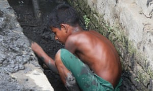 An 8-year old clears out the storm ditch ahead of the Monsoon season, in the Aung Ming Lar ghetto of Sittwe.