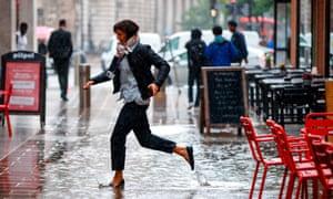 A pedestrian runs through a puddle