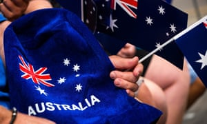 People wave flags and festive merchandise to celebrate Australia Day in Melbourne in 2017.