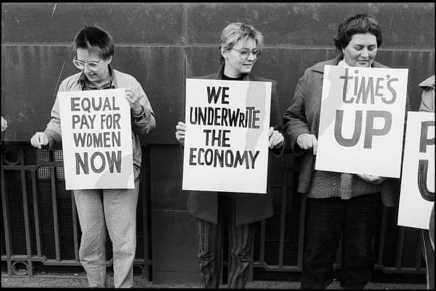 Women hold up banners