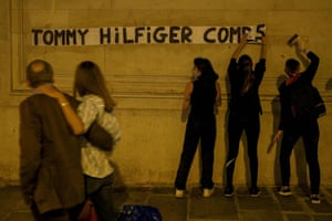 Members of a collective against violence towards women paste a banner in support of the Uighur population on a wall of the headquarters of the fashion brand Tommy Hilfiger in Paris, France