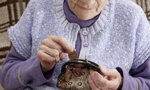 An older woman taking small change out of her purse.