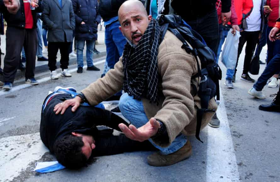 A demonstrator takes care of a man wounded by police in Tunis on 23 January.