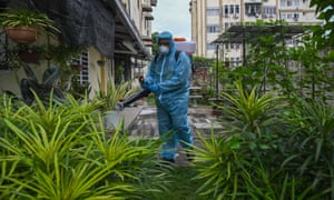 A council worker sprays disinfectant in the yard of an apartment building in Kuala Lumpur, Malaysia