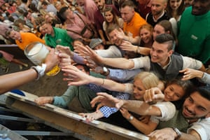 People reaching for a one-litre mug of beer on the first day of Oktoberfest
