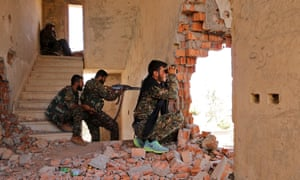 YPG fighters take up positions inside a damaged building